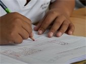 Image of child writing in notebook
